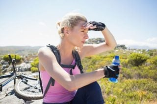 photo of woman cyclist holding bottle of energy drink