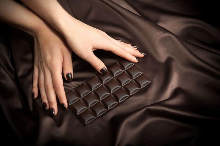 woman's hands holding dark chocolate bar