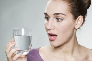 woman looking surprised at a glass of water