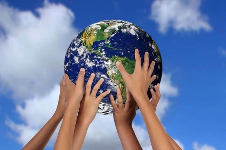 children's hands holding up a globe