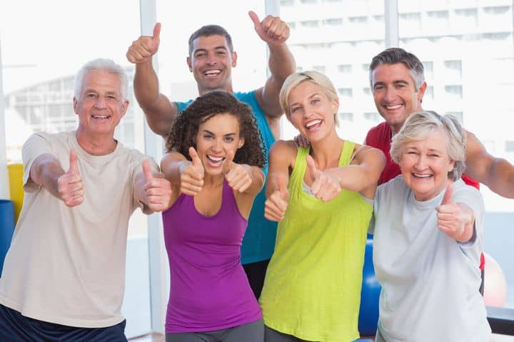 younger and older exercisers showing a thumbs-up sign