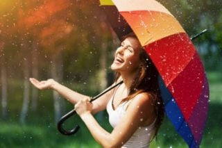 woman with umbrella laughing at the rain