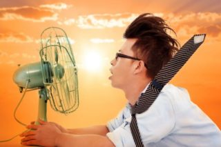 photo of hot man trying to get cool in front of fan