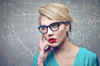 woman in front of blackboard covered with equations