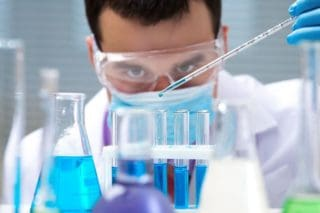 photo of scientist working with beakers and test tubes