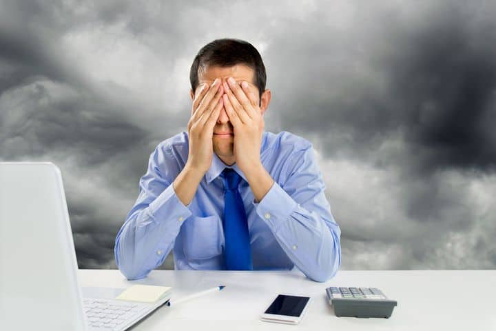 depiction of stressed man sitting at his work desk