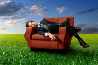 man sleeping in chair in a field of grass