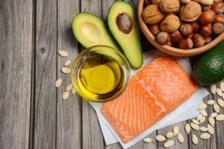 salmon, avocado, nuts, olive oil on a table