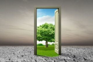 photo of doorway in barren landscape opening on to green field