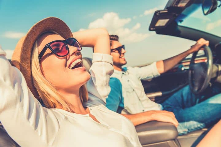 two people riding in convertible, laughing
