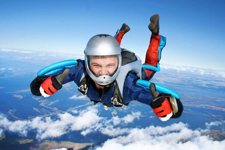 man giving thumbs up while skydiving