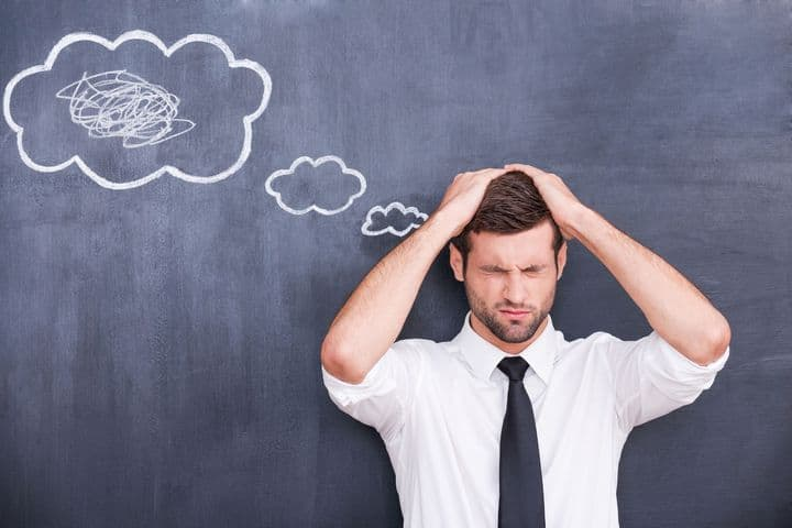 photo depicting stressed man holding head