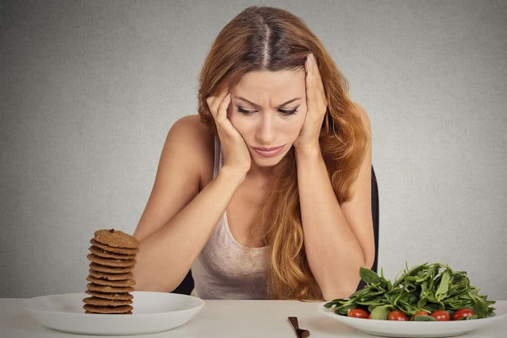 woman trying to choose between healthy and unhealthy foods