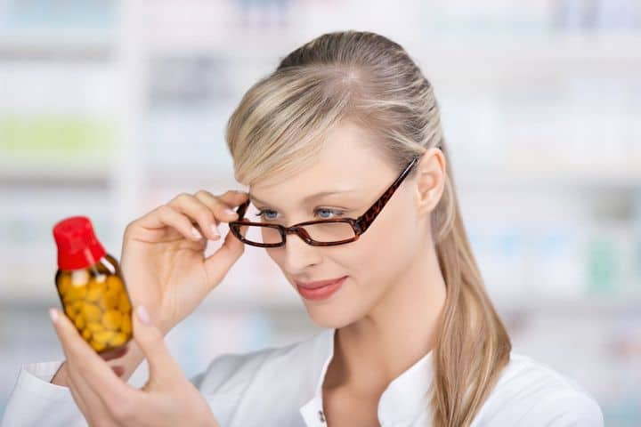 woman looking at a bottle of pills