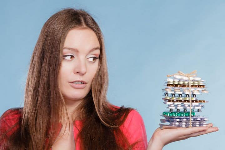 woman holding a stack of supplements