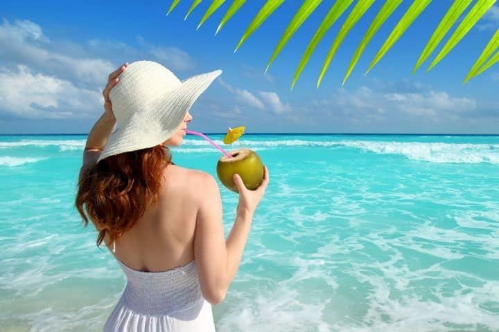 woman on beach drinking from coconut