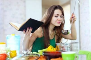 woman cooking with cookbook in hand