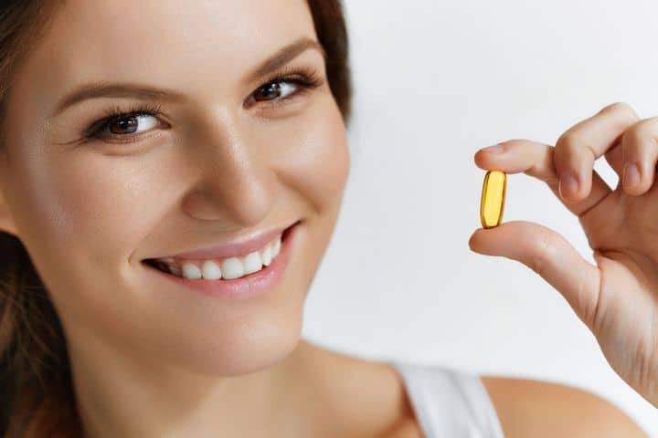 woman holding supplement capsule