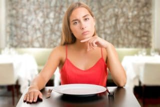 unhappy woman sitting behind an empty plate