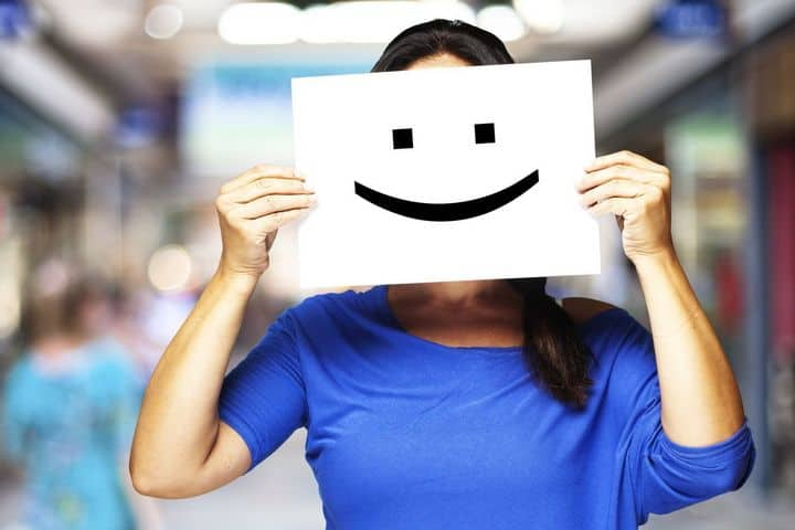 woman holding smile card in front of her face