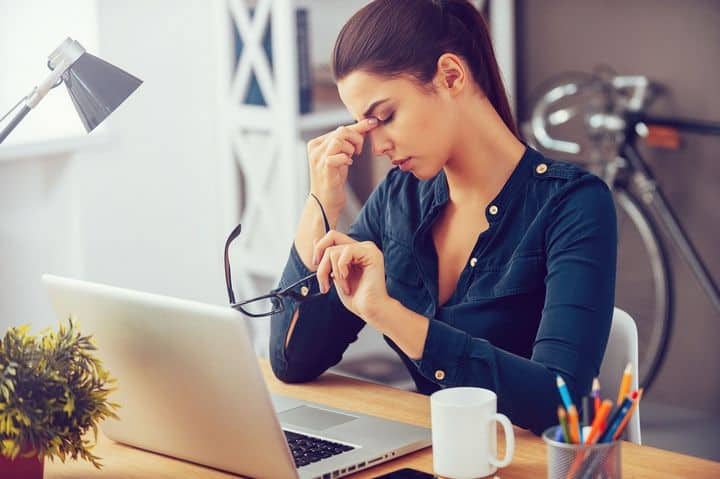 photo depicting woman sitting at work desk, pinching her nose, stressed