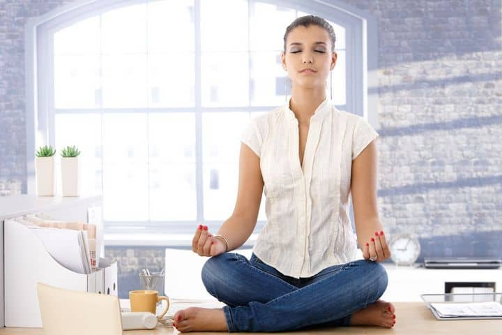 woman meditating on top of an office desk