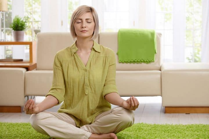 woman sitting meditating on the floor
