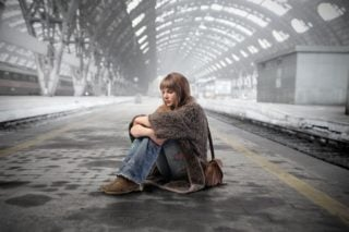 woman sitting on a train station platform