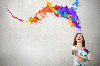 woman laughing at colorful paint swirls