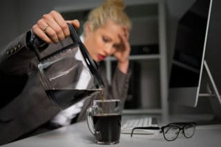 tired woman pouring cup of coffee