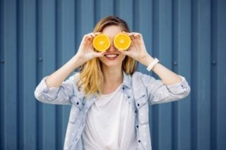 woman holding orange slices in front of her eyes