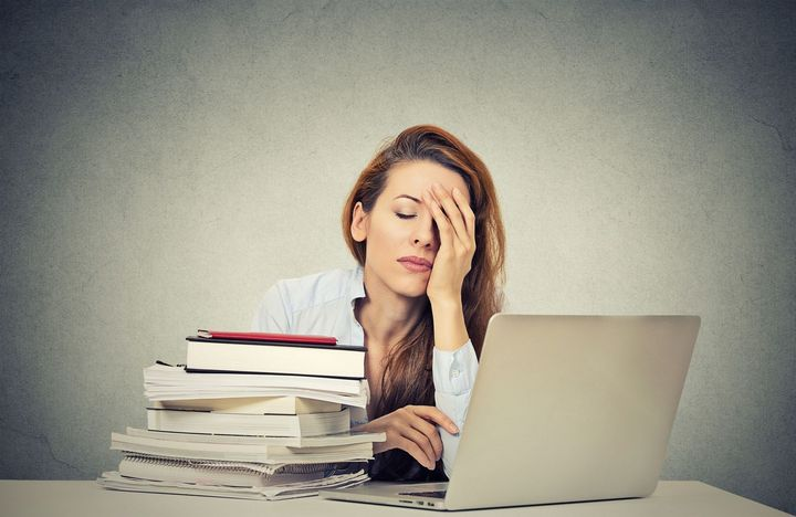 tired woman with books and laptop