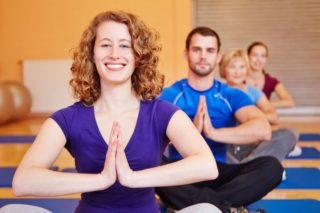 smiling woman in seated pose in yoga class