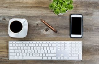 keyboard, smartphone, pen, plant, and coffee on desktop